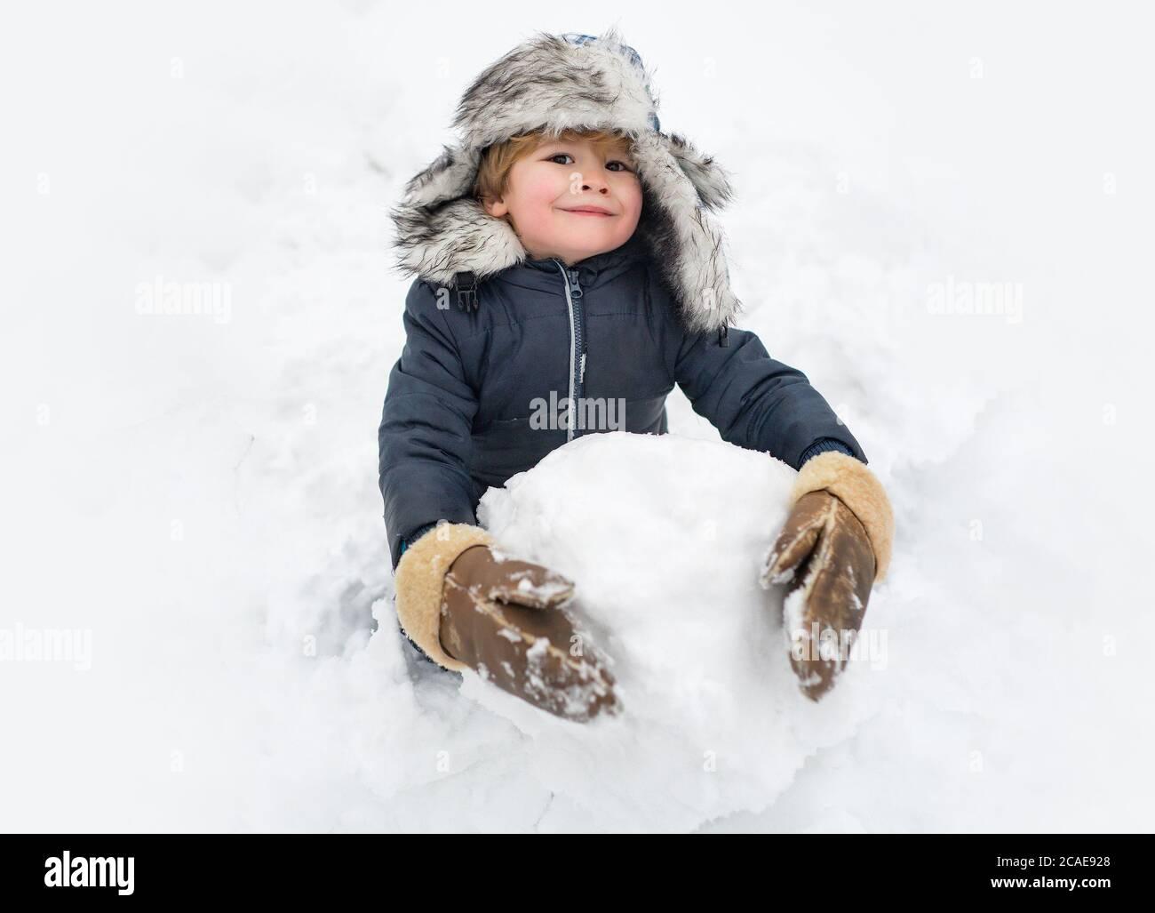 Lindo niño de pie en sombrero de invierno con nariz roja. Niño alegre Diversión y haciendo muñeco de nieve en Winter Park. Ropa de invierno para niños. Foto de stock