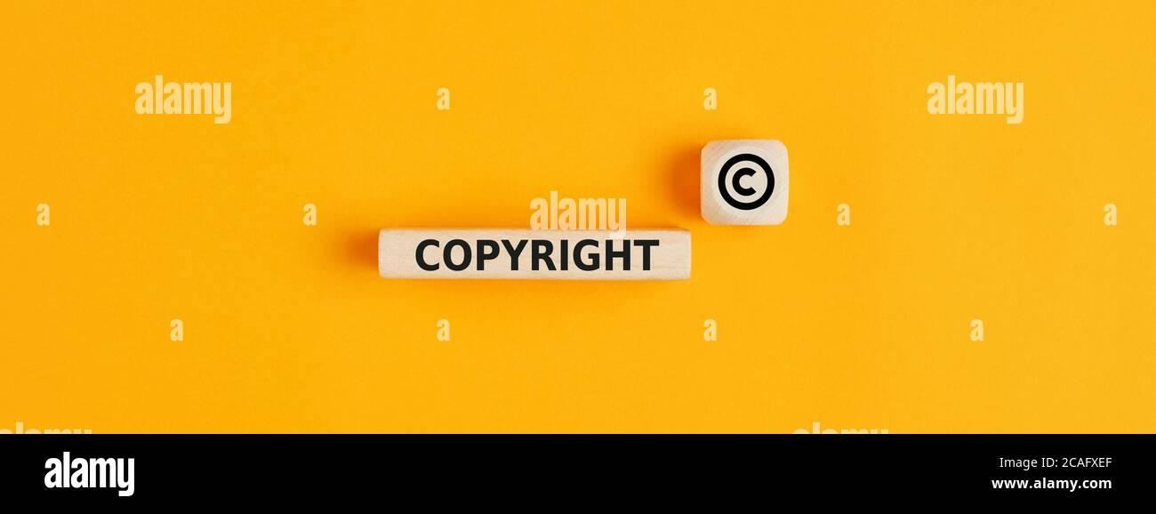 La palabra copyright y el símbolo de copyright en bloques de madera sobre fondo amarillo. Concepto de patente o protección del derecho de autor. Foto de stock