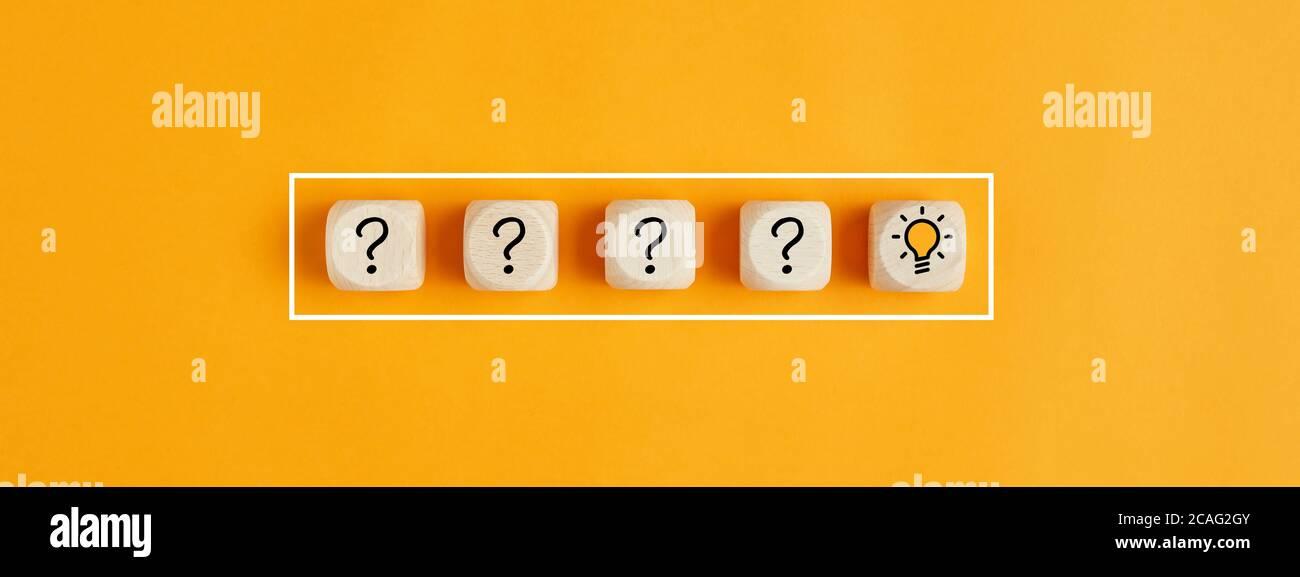 El proceso de resolución de problemas o formación de ideas. Signo de interrogación e iconos de bombilla sobre cubos de madera sobre fondo amarillo. Foto de stock