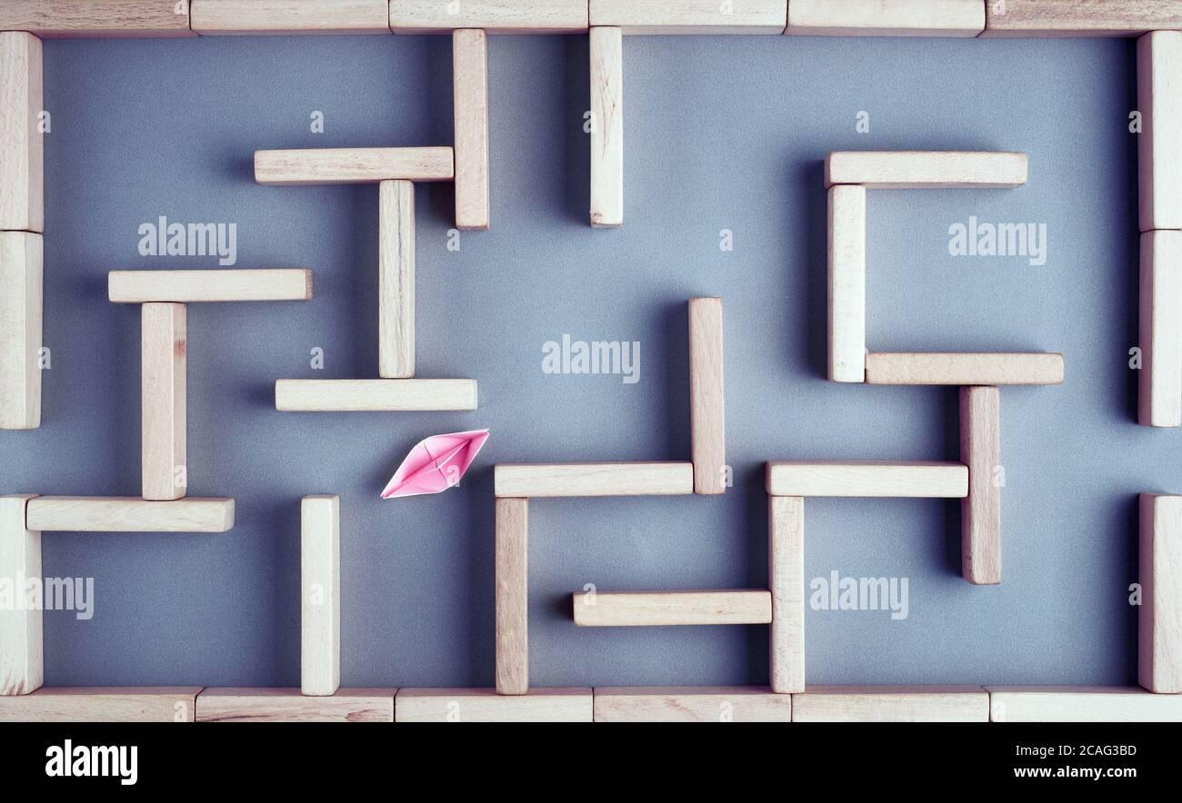 Barco de papel tratando de hacer su camino hacia la salida en un laberinto o laberinto hecho con bloques de madera. Lucha, desafío, solución o estrategia en busine Foto de stock