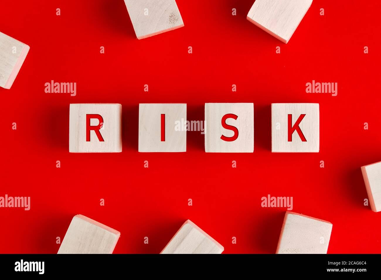 La palabra riesgo escrita sobre bloques de madera sobre fondo rojo. Concepto de gestión o evaluación de riesgos. Foto de stock