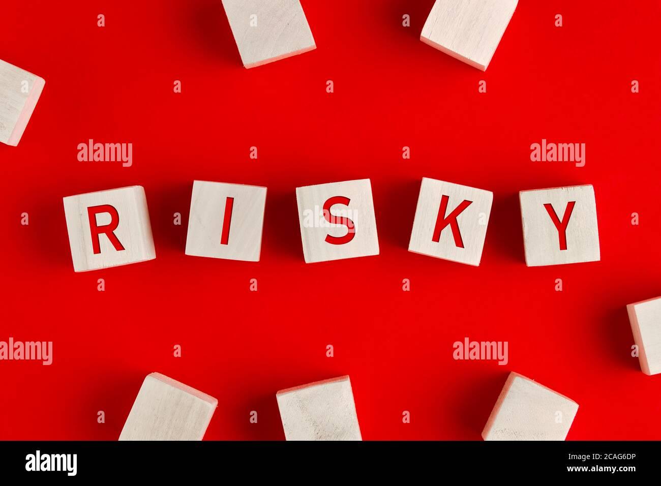 La palabra arriesgada escrita sobre bloques de madera sobre fondo rojo. Concepto de gestión de riesgos o evaluación y toma de decisiones en un negocio incierto envir Foto de stock