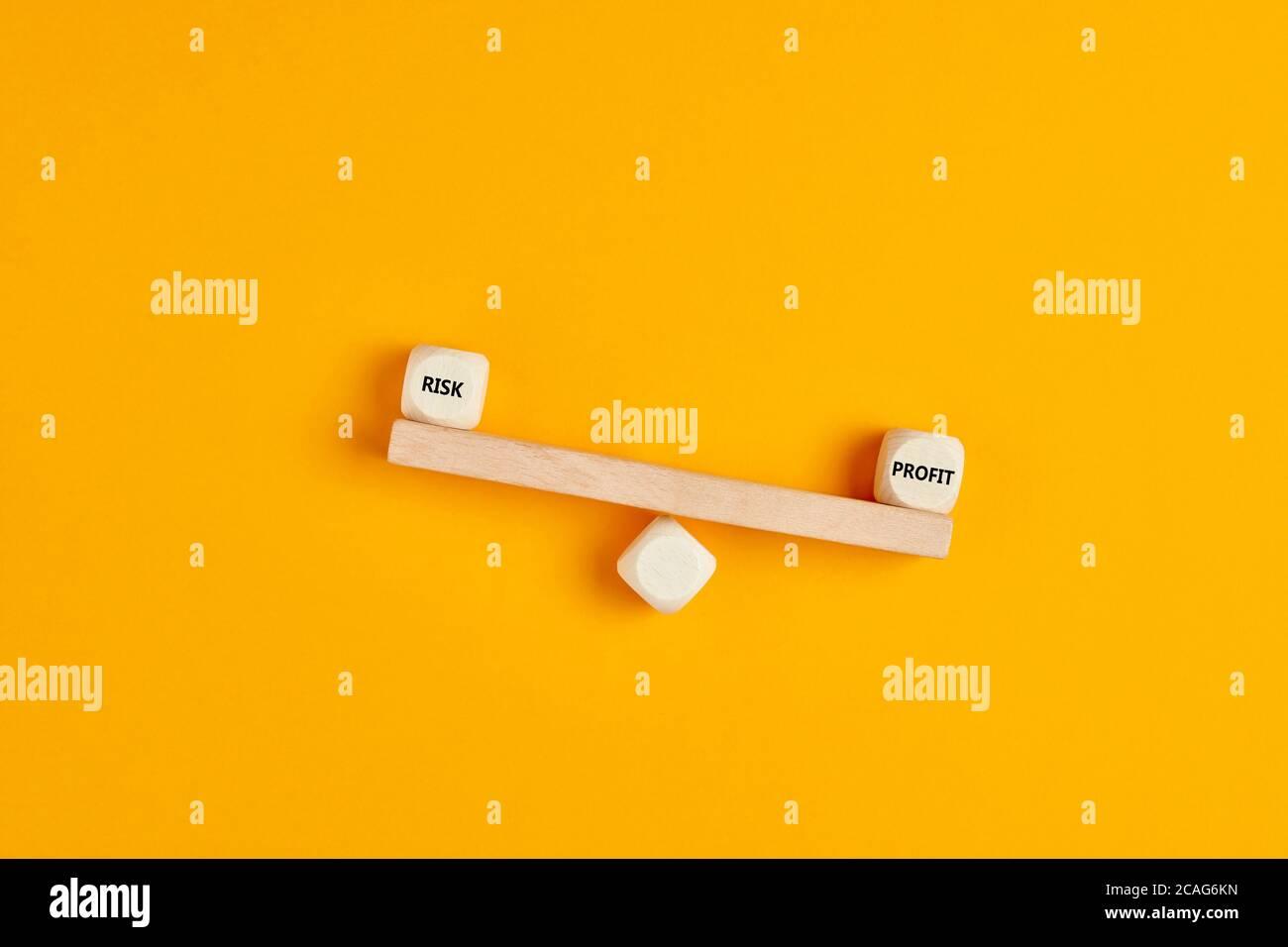 Las palabras beneficio y riesgo se escriben en una guacamaya hecha de bloques de madera sobre fondo amarillo. Concepto de análisis de beneficios y riesgos en negocios, financieros i Foto de stock