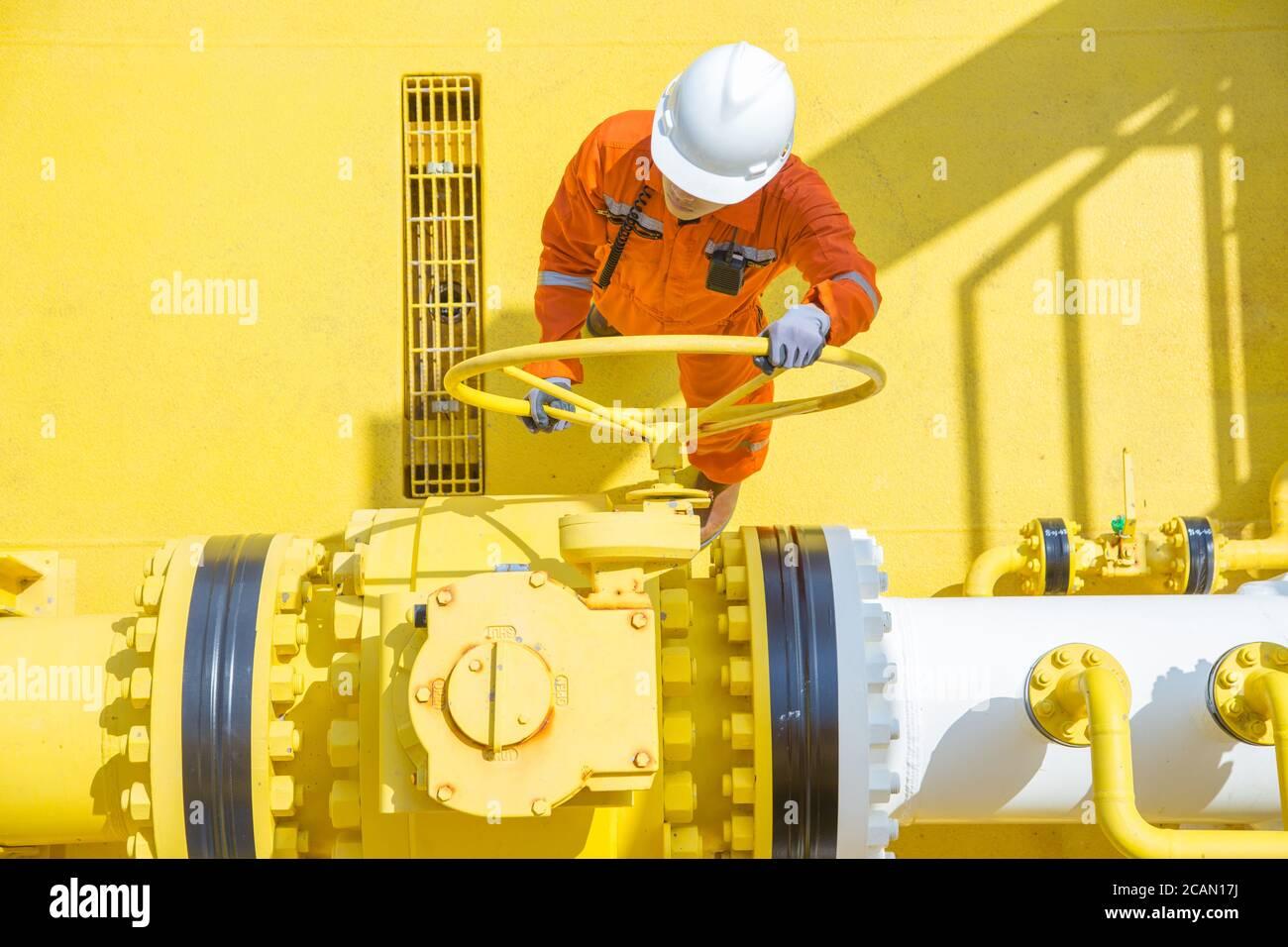 Operaciones de petróleo y gas en alta mar, el operador de producción abre la válvula para permitir el flujo de gas a la tubería de la línea del mar para el gas enviado y el petróleo crudo al procesamiento central Foto de stock