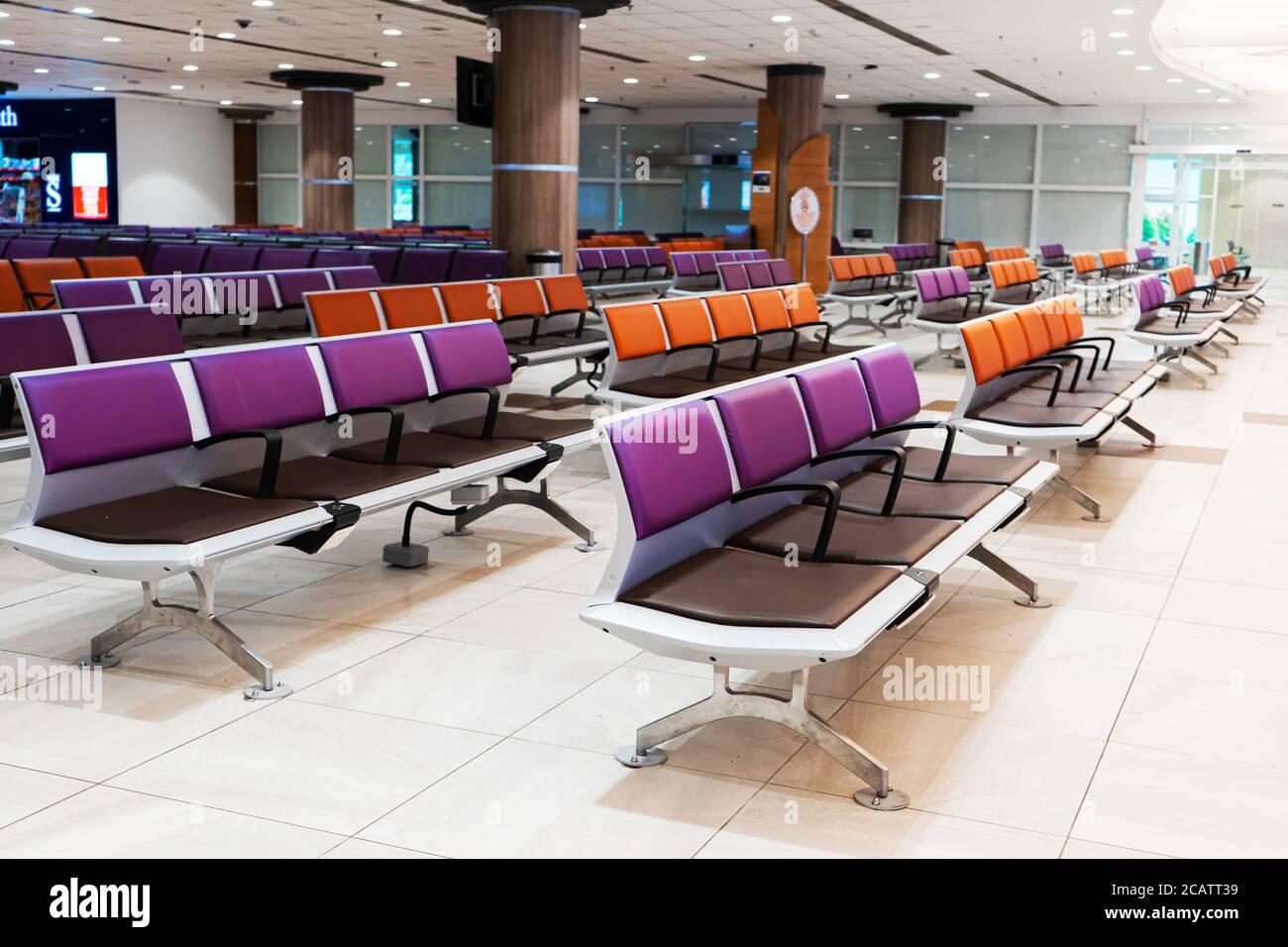 Vaciar el edificio del aeropuerto internacional durante una pandemia. Filas de asientos vacías en la sala del aeropuerto Foto de stock