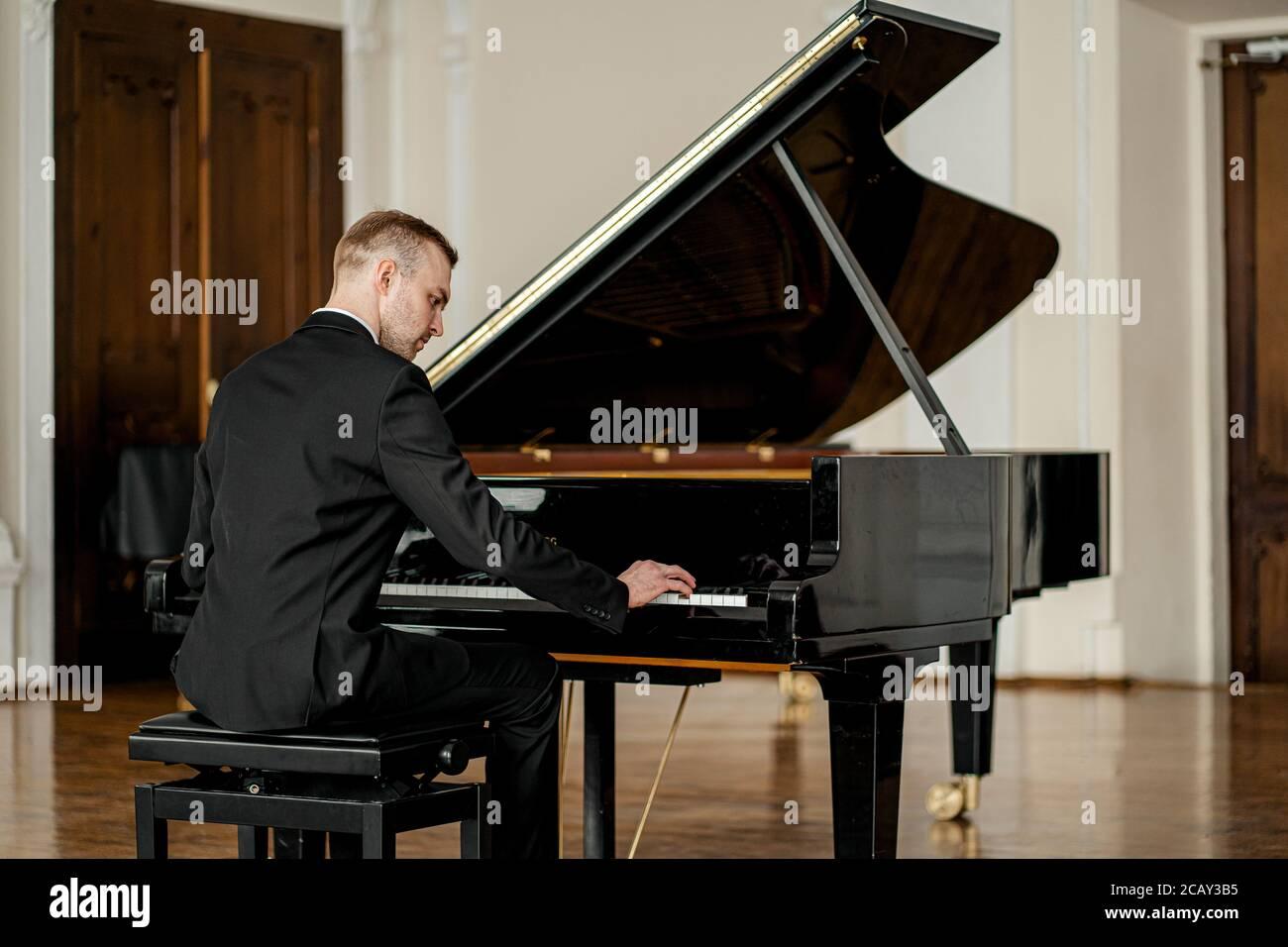 joven hombre caucásico guapo en traje elegante formal tocar piano con gracia. pianista profesional interpretar música clásica Foto de stock