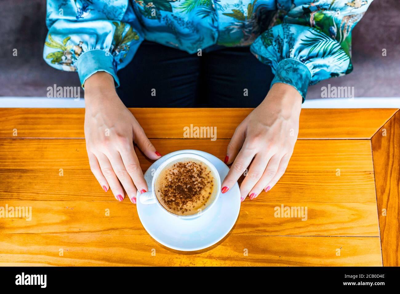 Vista desde la parte superior de dos manos de una mujer con un esmalte rojo mientras bebe un capuchino en un Cafetería local en Lisboa Foto de stock