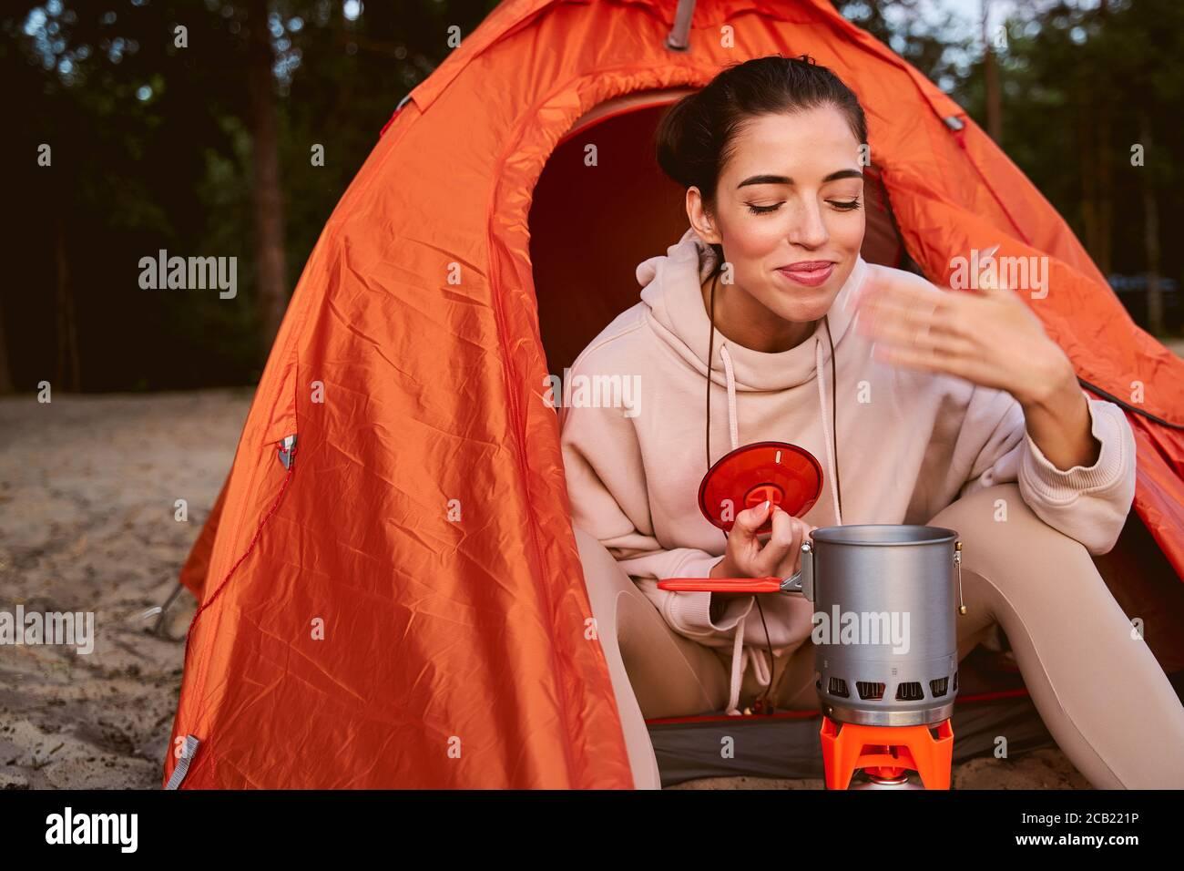 Encantadora joven que hace bebidas calientes durante el camping Foto de stock
