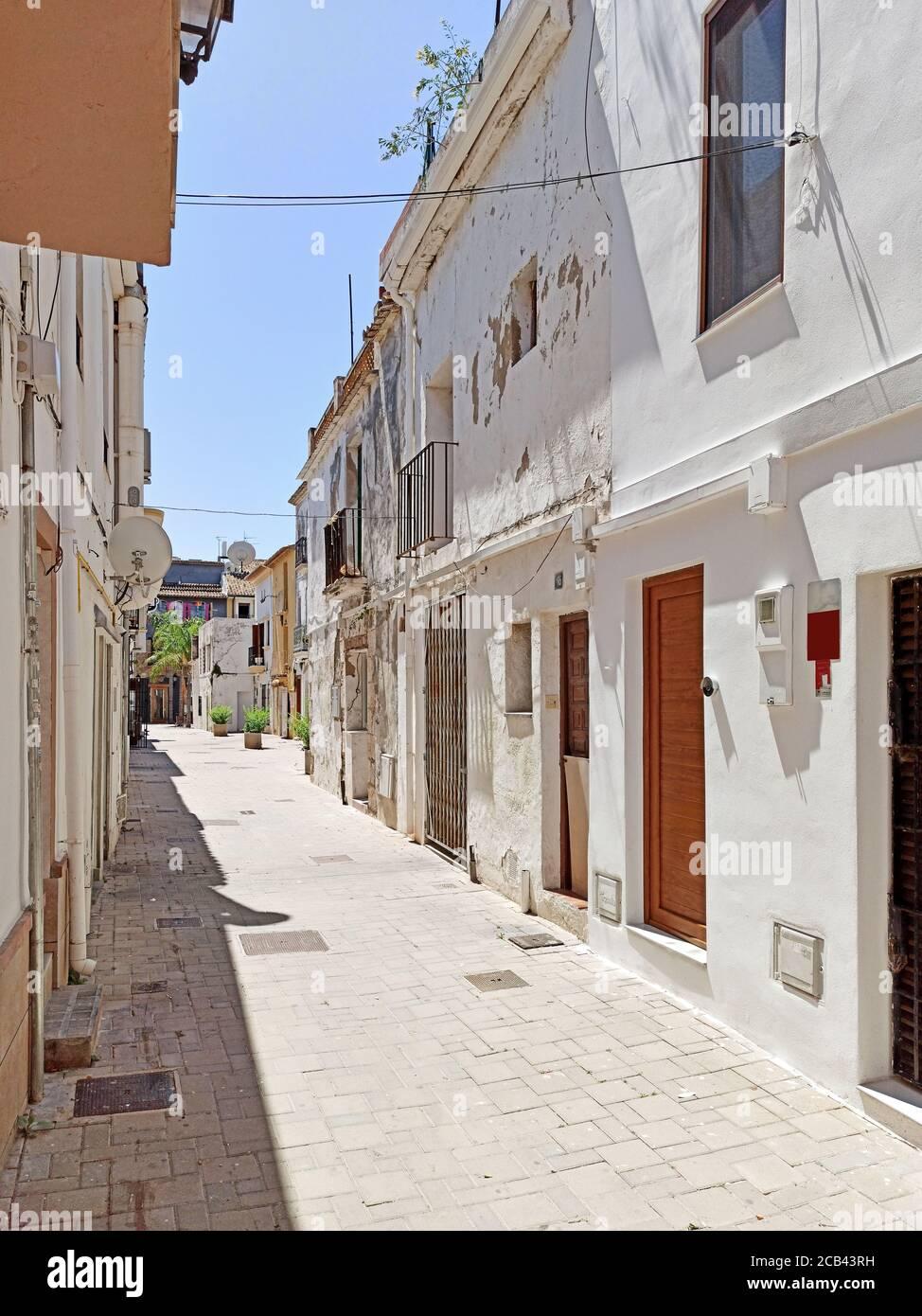 Encantadora calle encalada blanca durante el caluroso día de verano de la ciudad turística turística turística de Denia. Comunidad Valenciana, Provincia de Alicante, Foto de stock