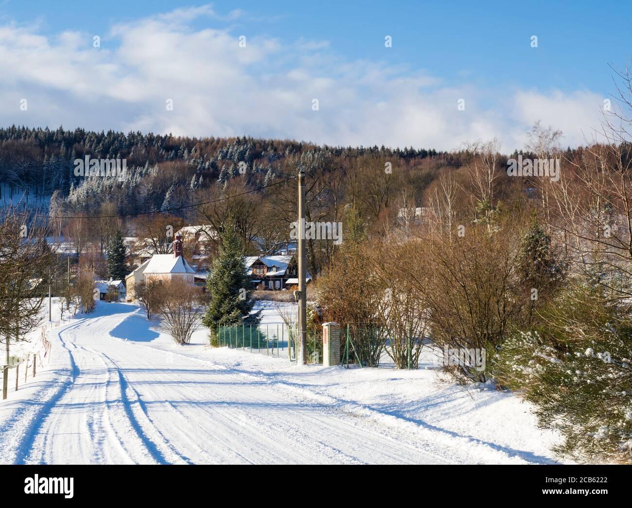 vista de invierno en el pueblo travnik con capilla, casa de madera y árboles, paisaje rural cubierto de nieve con en luzicke hory montaña Foto de stock