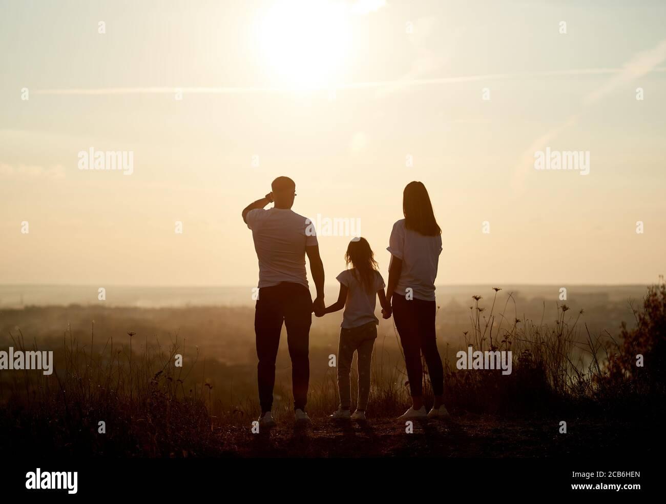 Silueta de una familia - padre, madre e hija de pie en la colina con sus espaldas a la cámara y mirando al horizonte en la puesta de sol Foto de stock