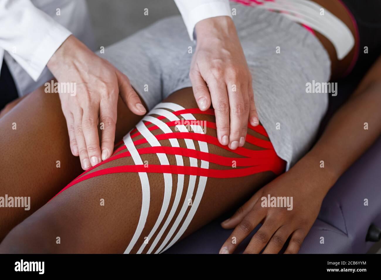 Grabación de Kinesiología. Fisioterapeuta aplicando cinta de cinesiología a las caderas del paciente.terapeuta tratando a una joven atleta afroamericana. Post traumático Foto de stock