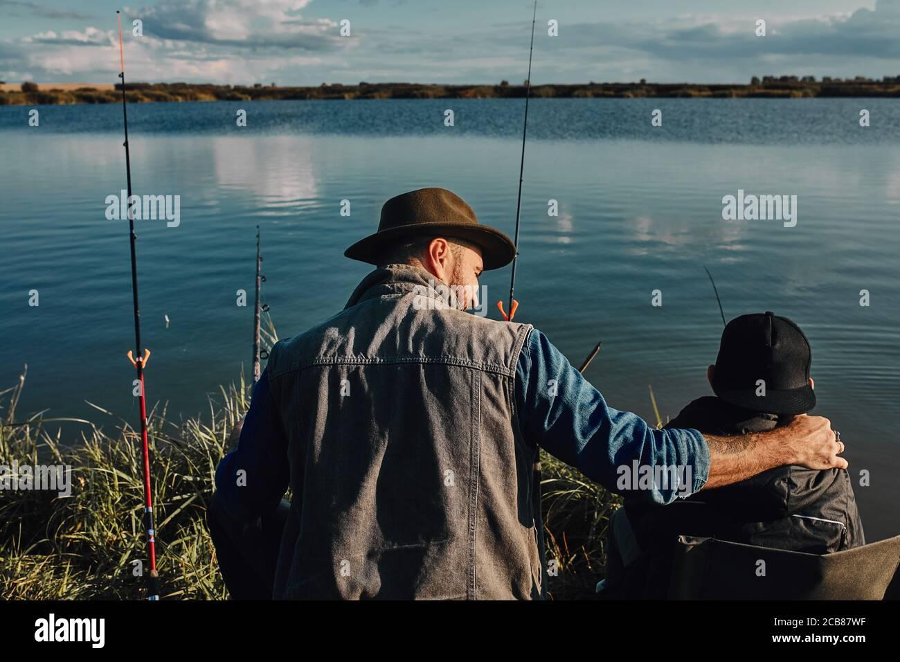 Las espaldas del padre y el hijo caucásicos se sientan cerca del lago en sillas de pesca. Están felices de pasar tiempo juntos. Cálido día soleado. Foto de stock
