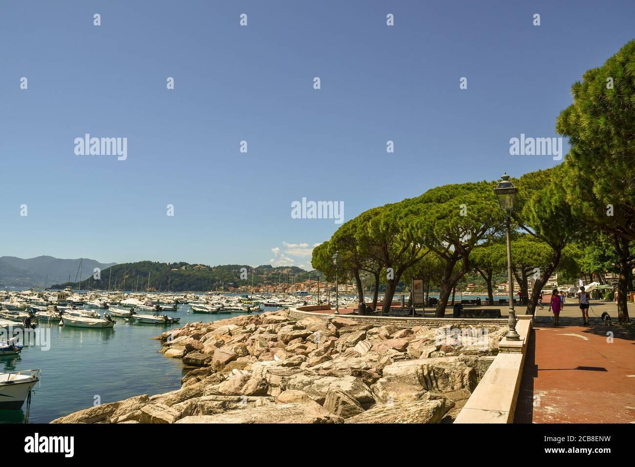 Vista del paseo marítimo con gente caminando y el puerto de la ciudad marítima en la orilla del Golfo de los Poets, Lerici, la Spezia, Italia Foto de stock