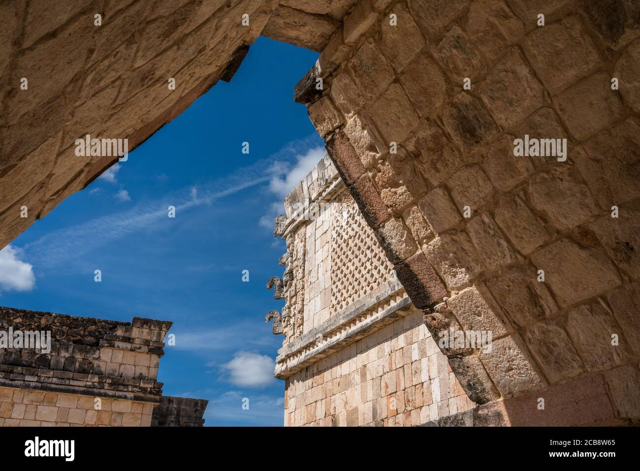 La vista a través de un arco en el Cuadrángulo de las aves en las ruinas de la ciudad maya de Uxmal en Yucatán, México. Las máscaras Chaac adornan la esquina de t Foto de stock