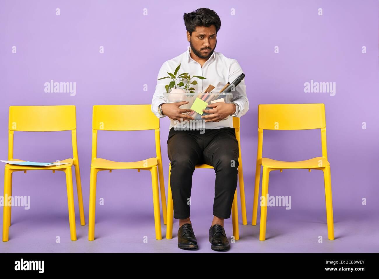 Retrato de triste joven de piel oscura que sostiene caja de personal las pertenencias son despedido del trabajo Foto de stock