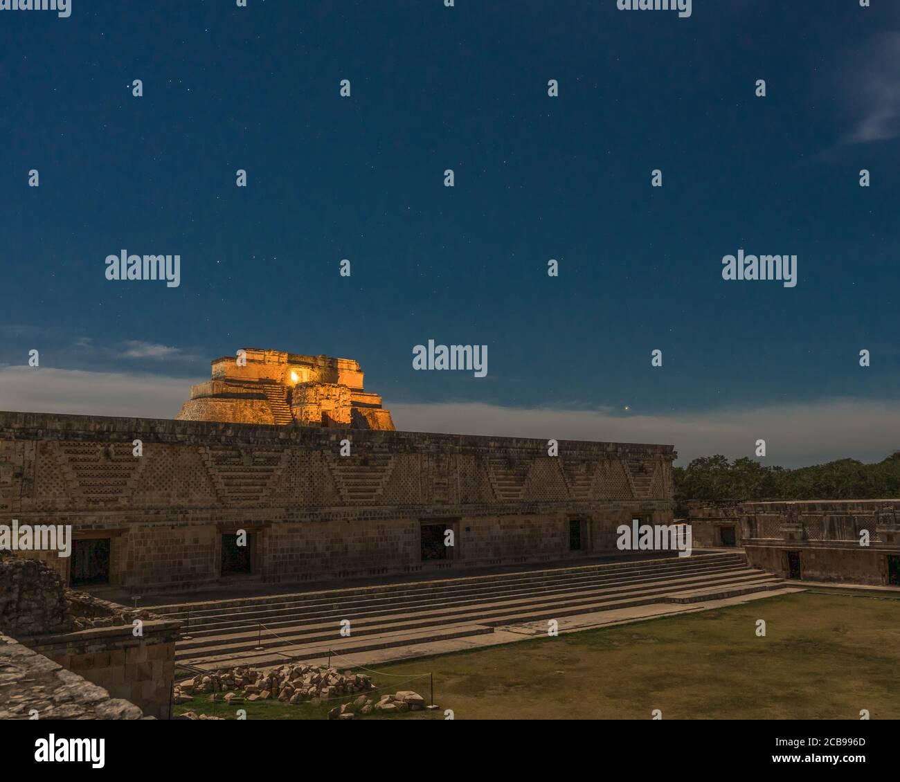 La Pirámide del Mago detrás del edificio este del Cuadrángulo de las Monjas está iluminado en las ruinas mayas prehispánicas de Uxmal, México. Foto de stock