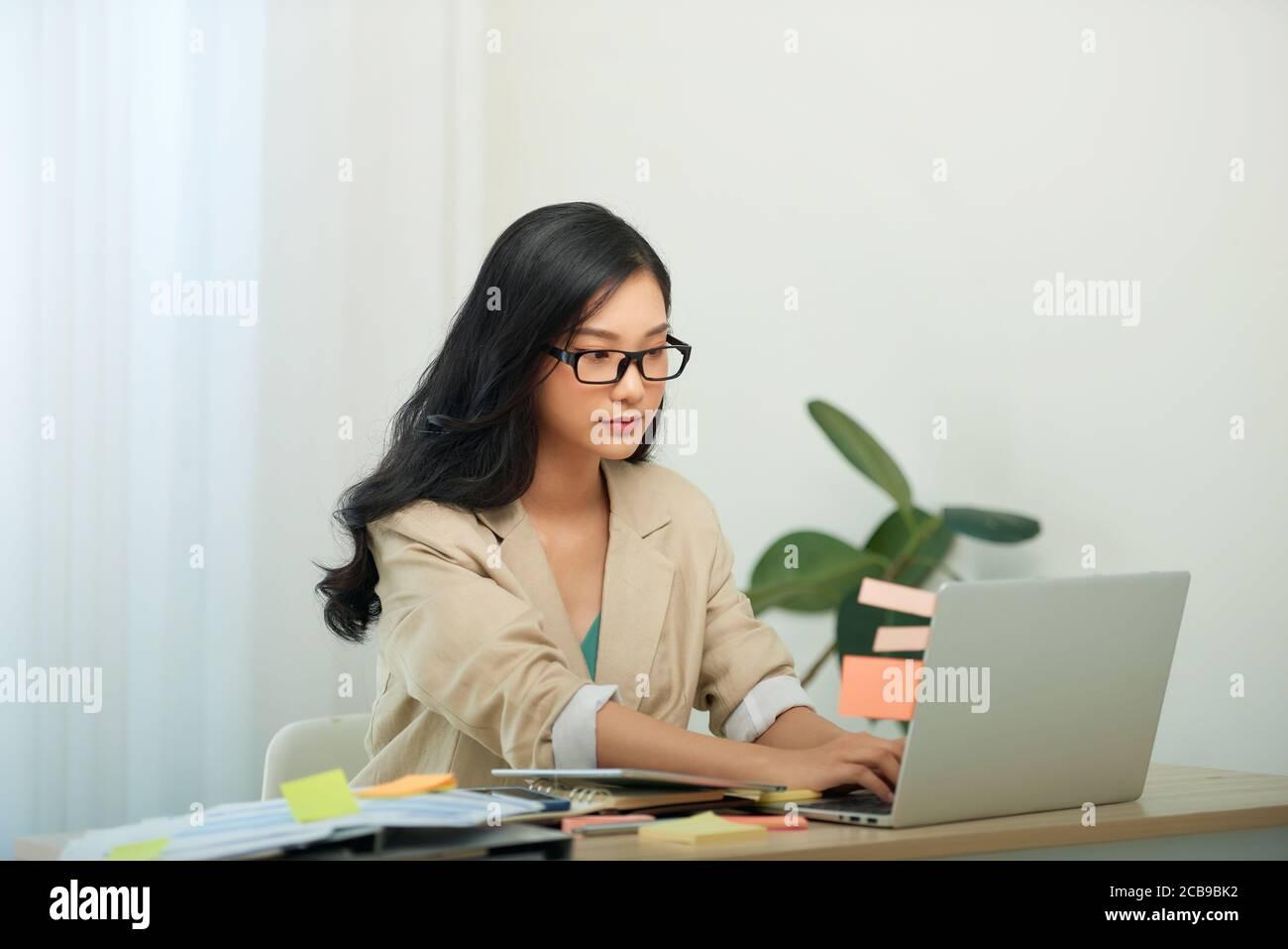 Head shot agradable mujer joven feliz trabajando en la computadora en casa. Foto de stock