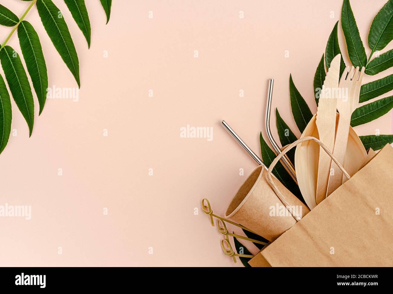 Juego libre de plástico con bambú, cubiertos de papel y pajitas de metal sobre fondo rosa. Concepto de cero residuos. Foto de stock