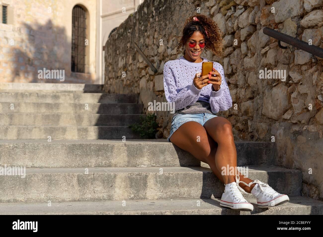 Retrato de una atractiva mujer negra joven tomando un selfie con su móvil. Hablando por teléfono sentado en las escaleras Foto de stock