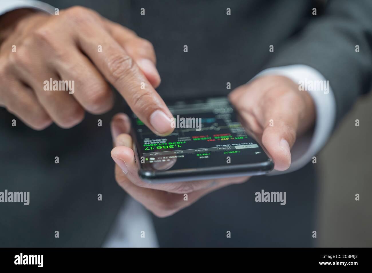 Primer plano de las manos humanas que comprueban las cartas de acciones financieras en. Foto de stock