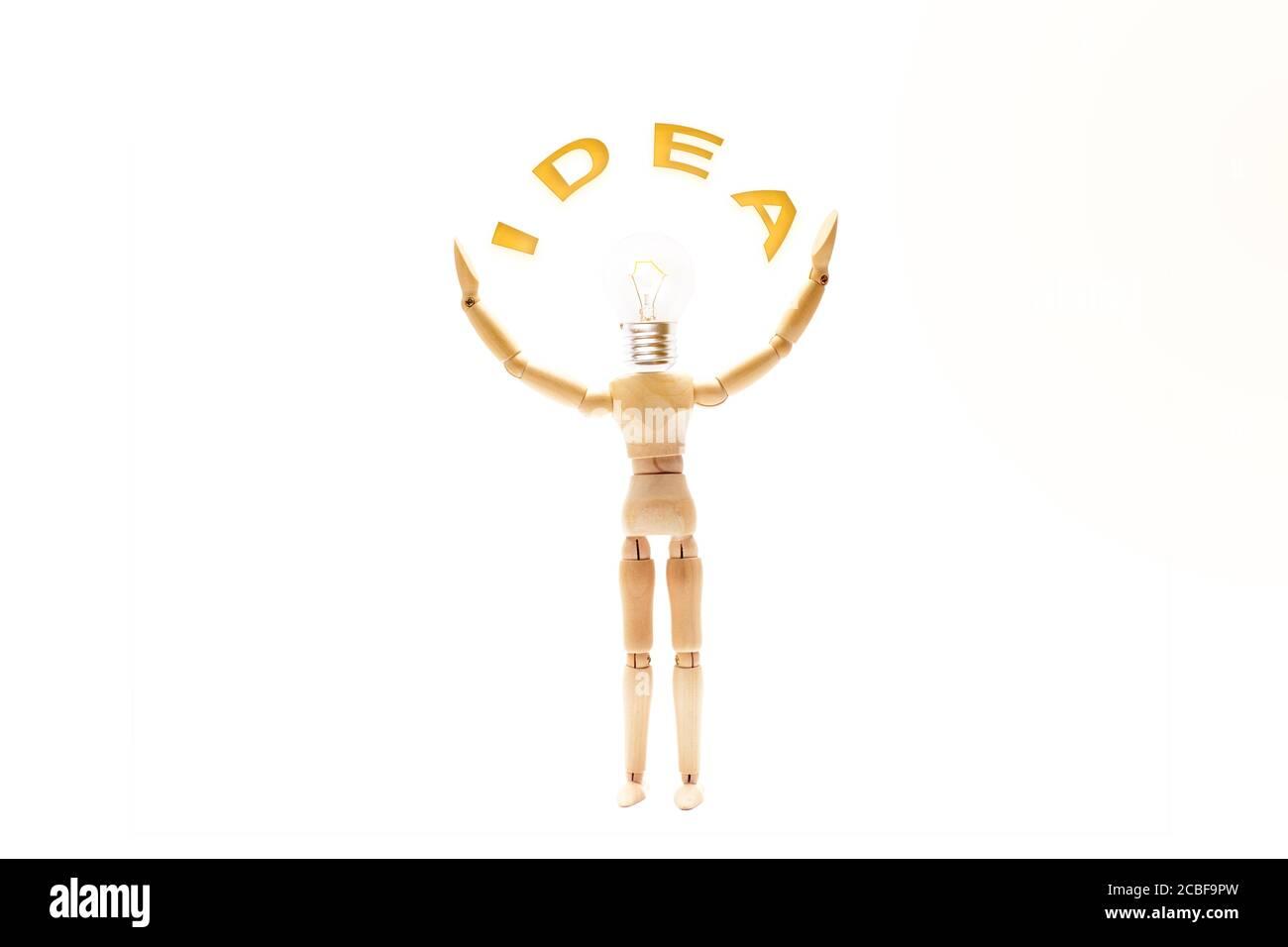 Maniquí con la cabeza de la bombilla y los brazos arriba sosteniendo la palabra IDEA. Concepto creativo e innovación Foto de stock