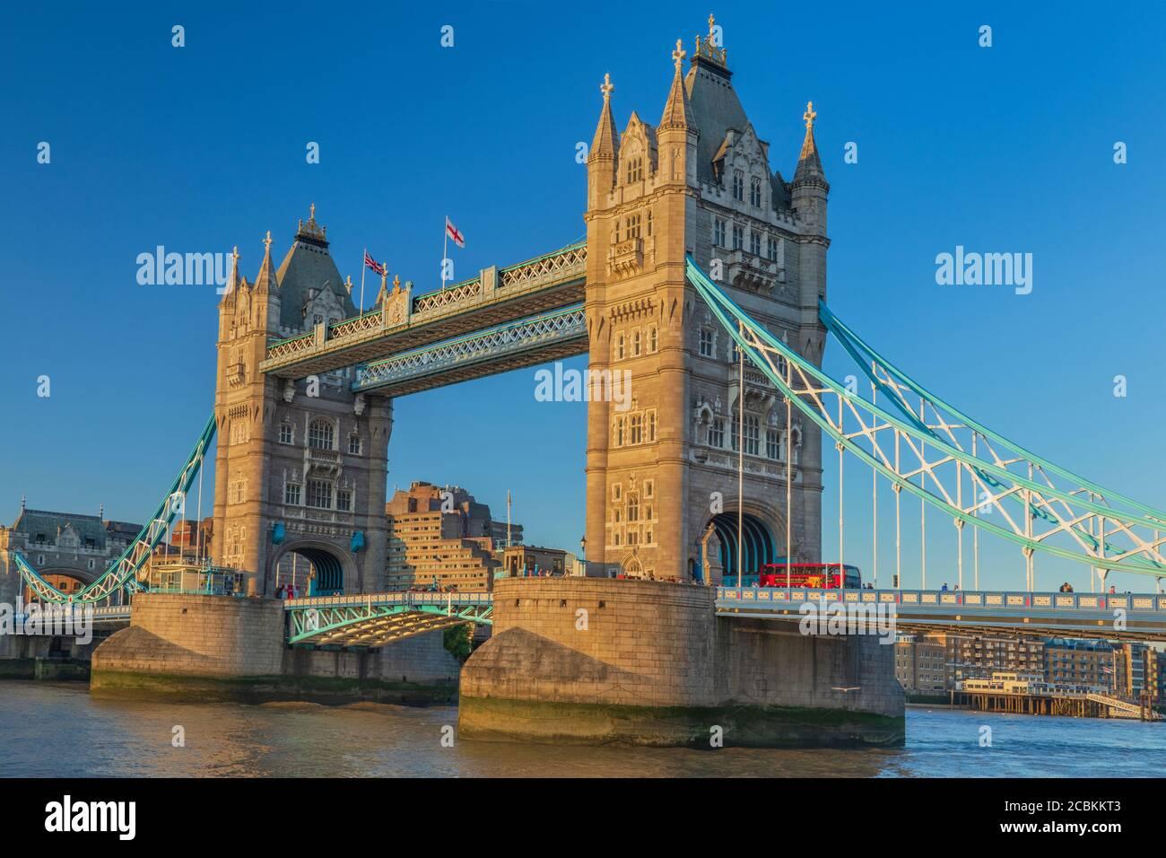 Inglaterra, Londres, Tower Bridge en la luz de la noche visto desde la orilla sur del río Támesis con un icónico autobús rojo de Londres cruzando el puente. Foto de stock