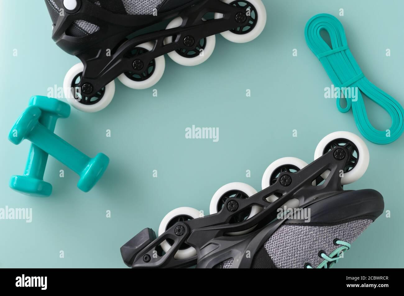 Estilo de vida activo y borde de fitness con pesas, patines y banda de resistencia sobre fondo verde Foto de stock