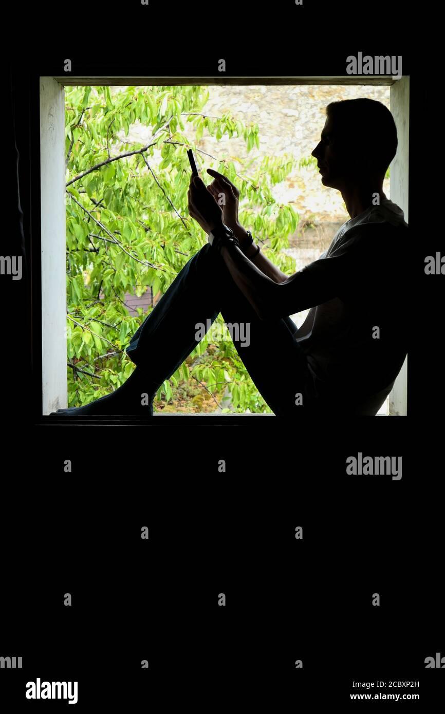 Persona que utiliza tecnología. Silueta de un hombre en el interior de una ventana, con un smartphone en sus manos. Foto de stock