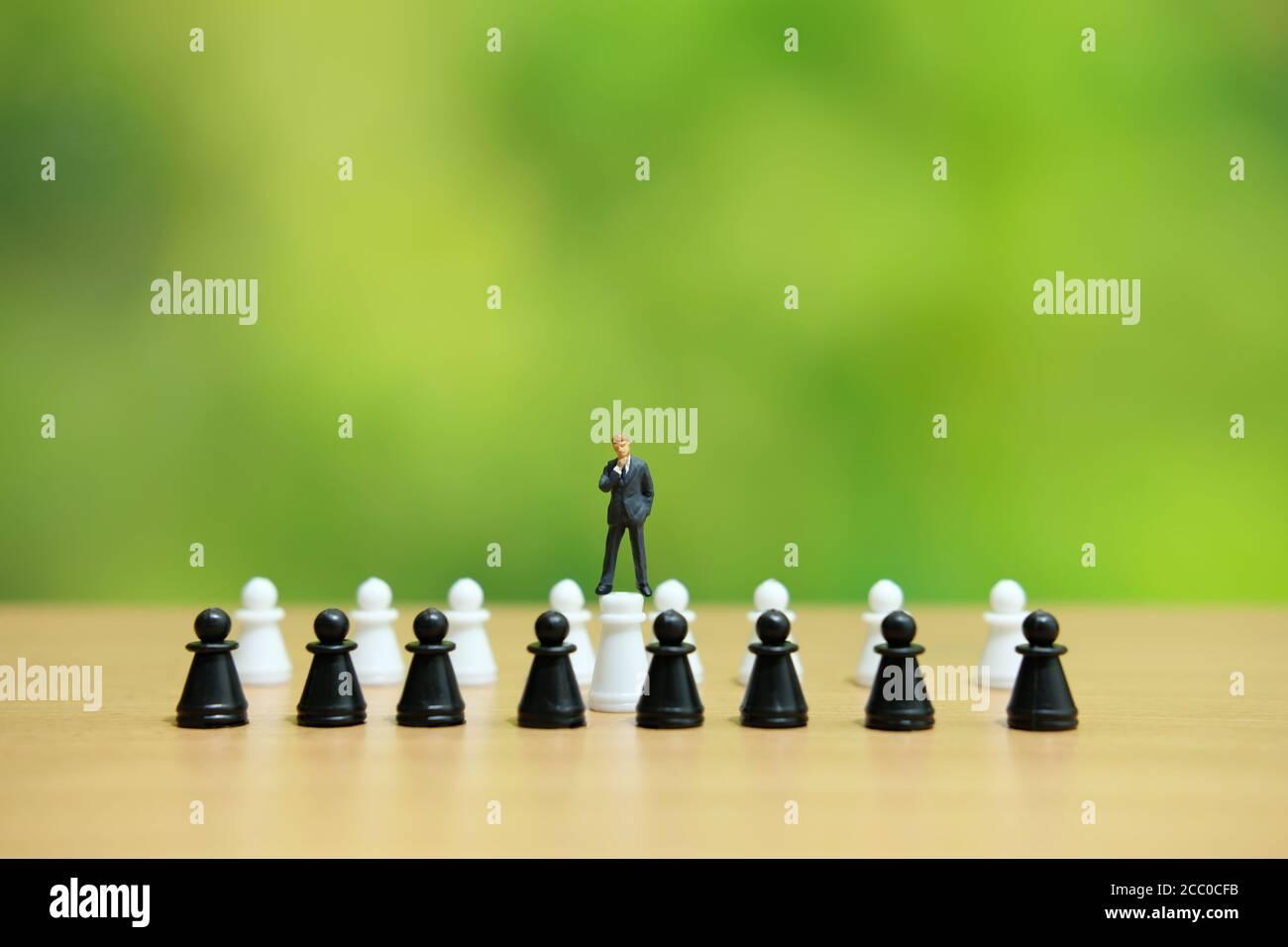 Minihombre concepto estratégico - hombre de negocios de pie sobre el peón de ajedrez Foto de stock