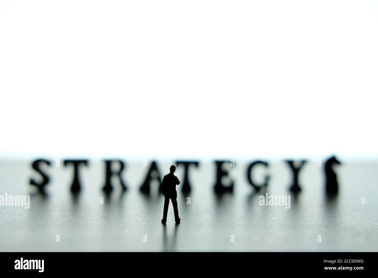Silueta de hombres de negocios en miniatura de pie y pensando frente a rompecabezas de bloques de palabras de estrategia Foto de stock