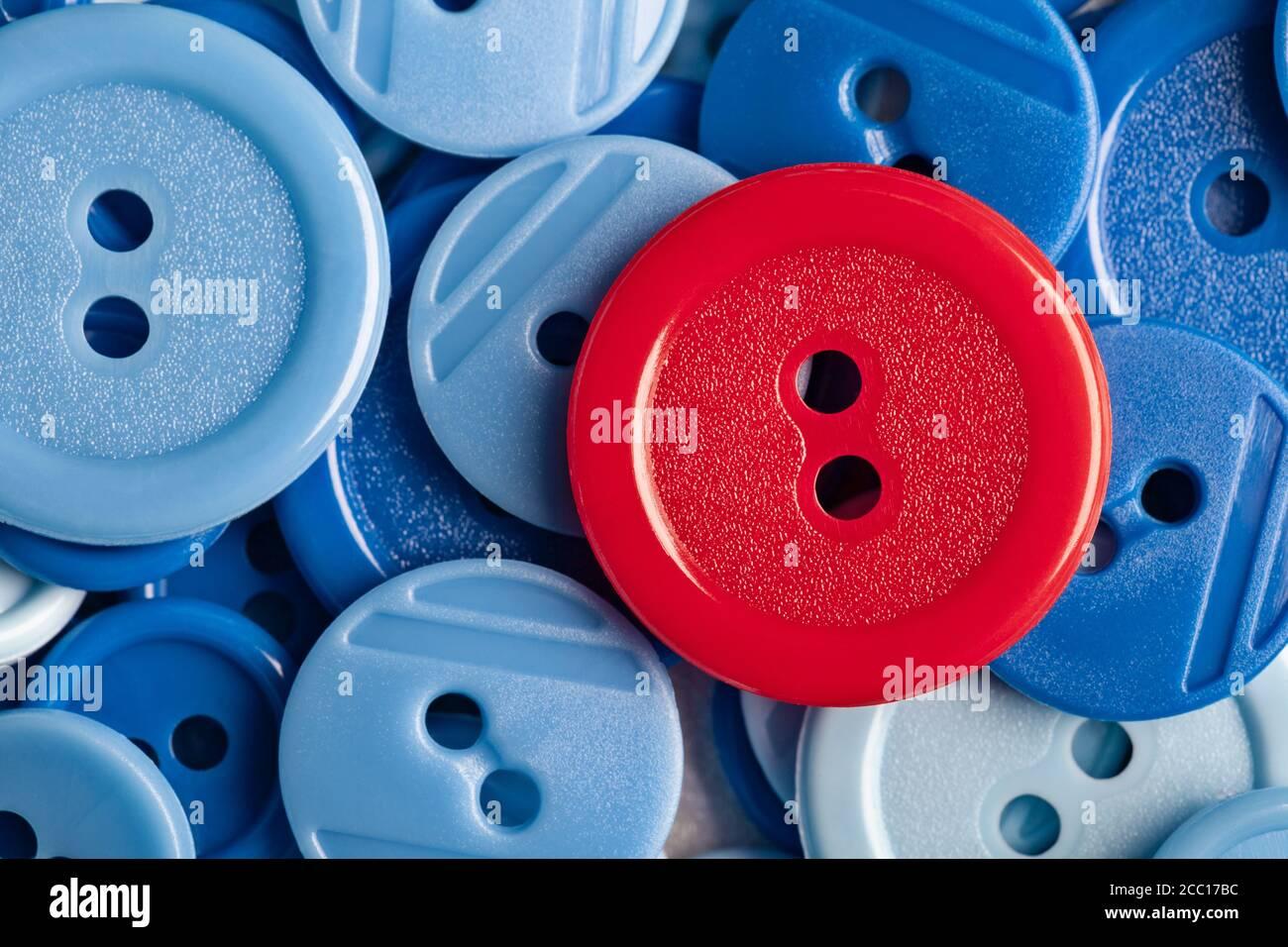 Botón rojo sobre fondo de botones de plástico azul. Este archivo se limpia y se vuelve a archivar. Foto de stock