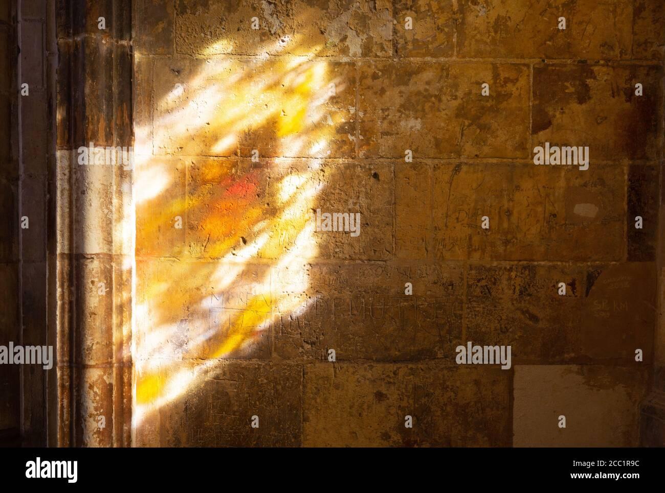 Concepto de religión; una vidriera que arrojaba una luz colorida sobre las paredes medievales de los claustros, Tours Catedral, Tours Francia Foto de stock