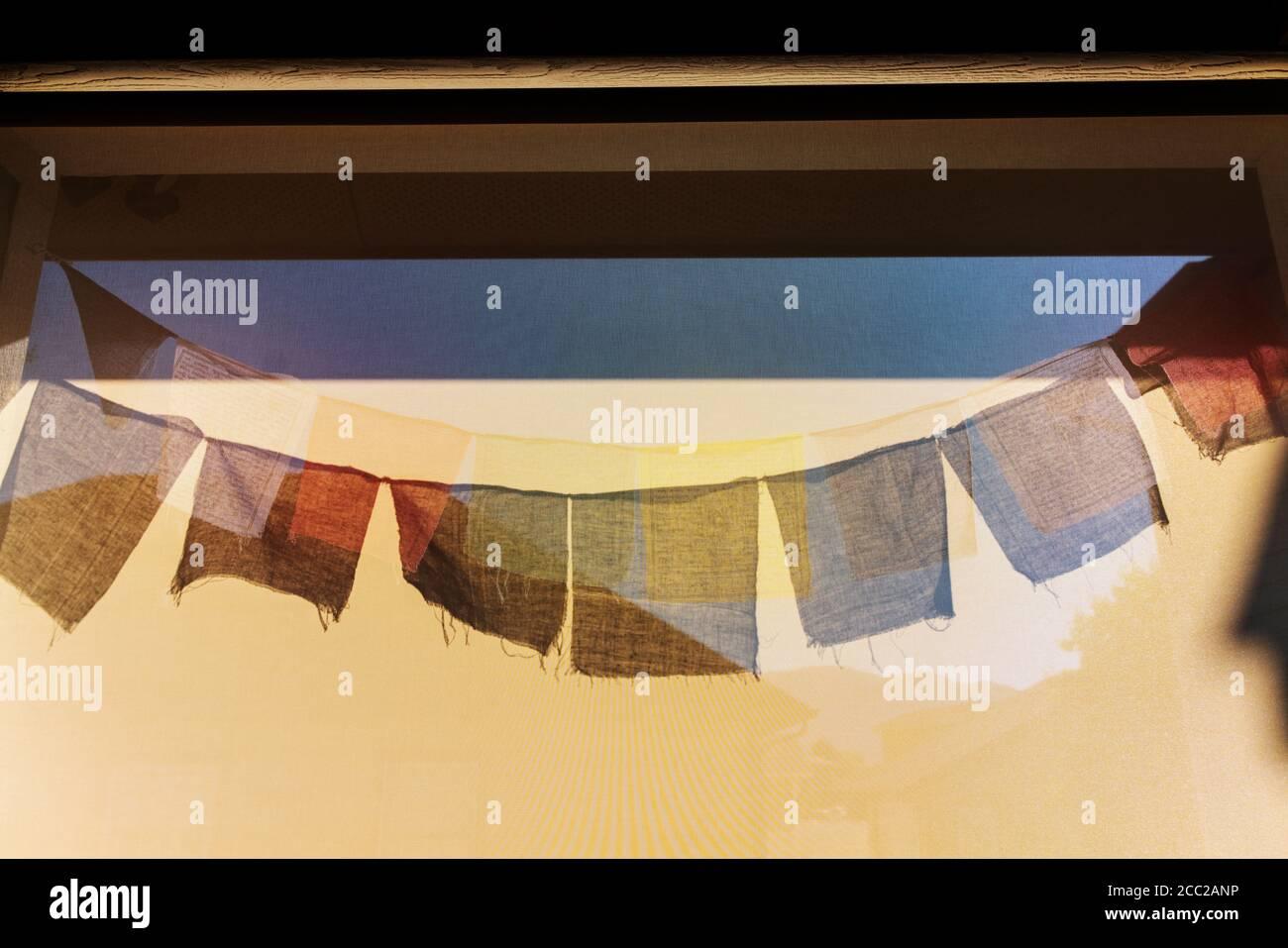 El sol proyecta sombras de las banderas de oración budistas tradicionales sobre un pantalla de viento Foto de stock