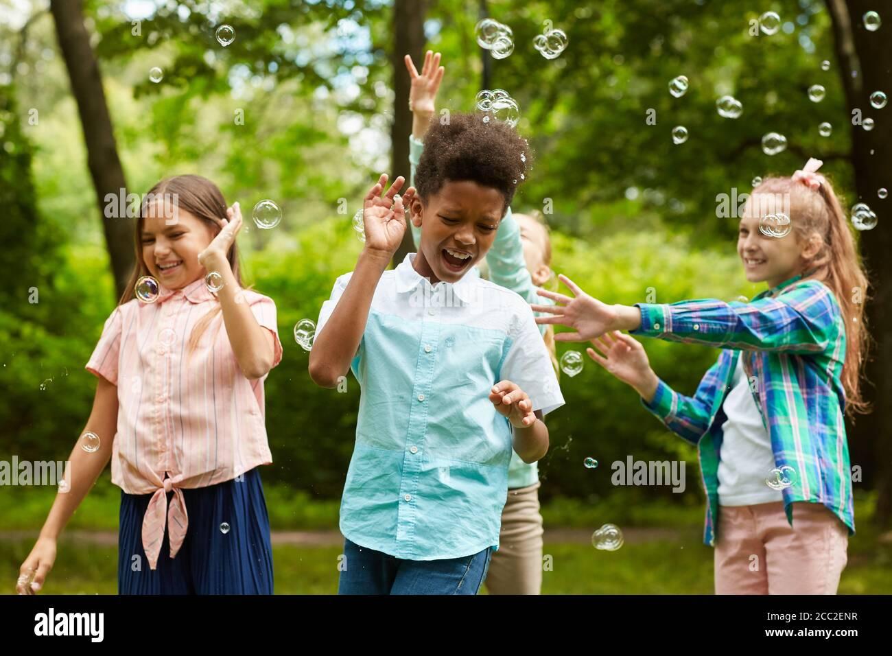 Retrato de cintura arriba de un grupo multiétnico de niños sin preocupaciones jugando con burbujas al aire libre en el parque Foto de stock