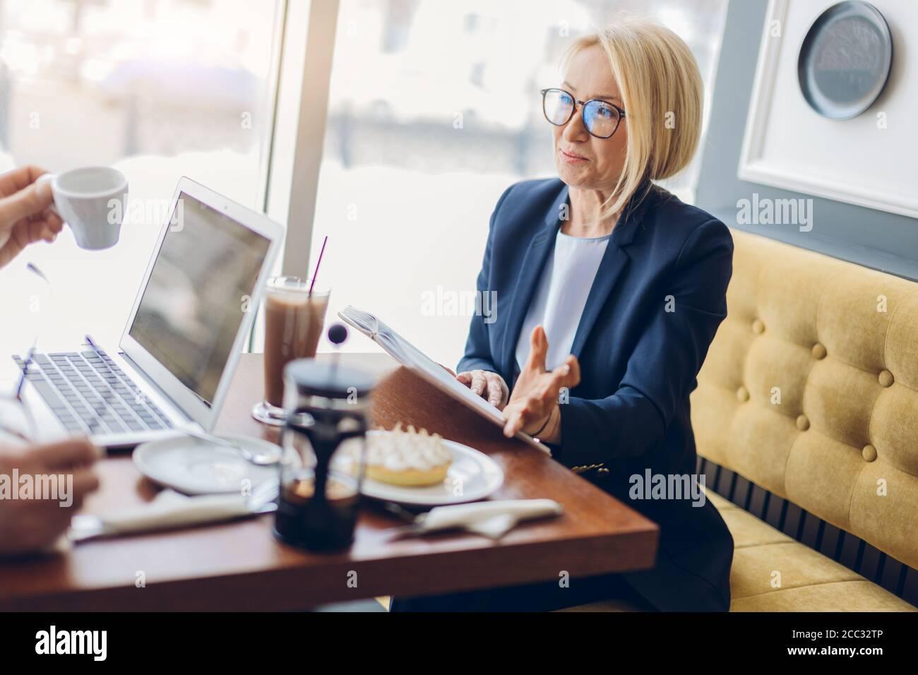 mujer de negocios de éxito compartiendo con sus secretos de negocio. de cerca vista lateral foto. mujer de edad encantadora hablando con un cliente en el café Foto de stock