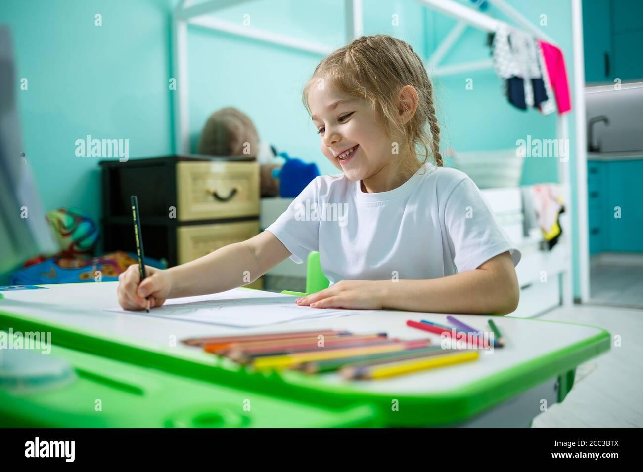 Una chica en una camiseta blanca se sienta en su habitación en la mesa y dibuja con lápices de colores Foto de stock