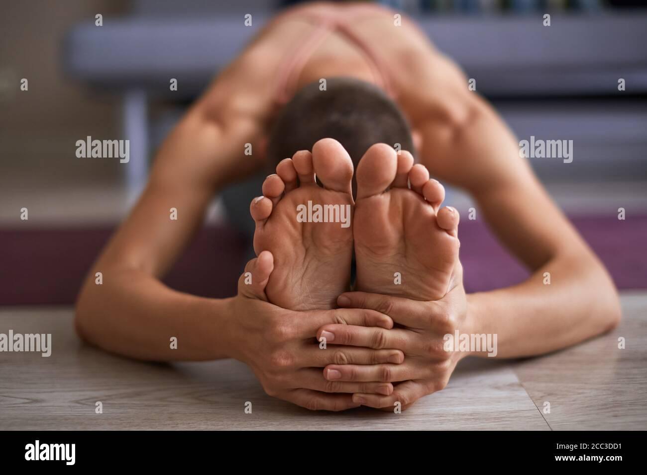 Cerca de los pies femeninos, mientras que el estiramiento de la alfombrilla. Estiramiento sentado en ejercicio de inclinación hacia adelante, paschimottanasana pose. Mujer vestida en ropa deportiva Foto de stock