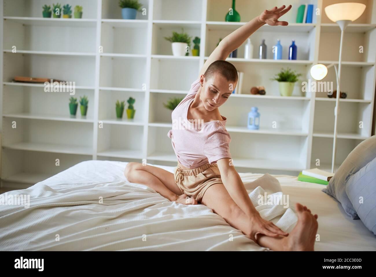 Encantador y smilng mujer fitness en pijama haciendo ejercicios en casa en la cama. Concepto de estilo de vida saludable Foto de stock