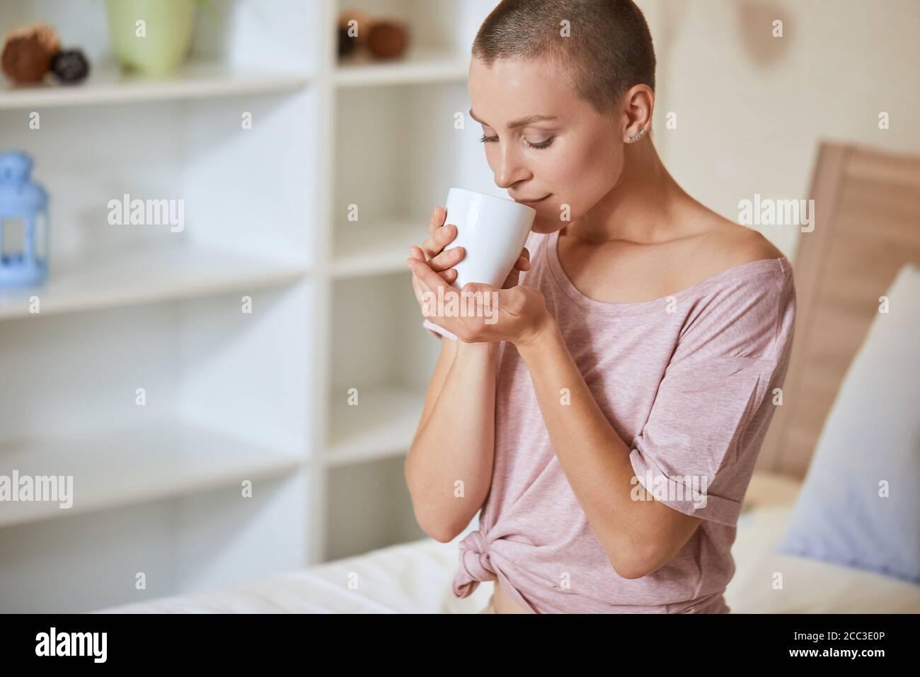 Hermosa joven con pelo corto sentarse en la cama en la habitación de luz y disfrutar de beber té o café por la mañana en casa. Foto de stock