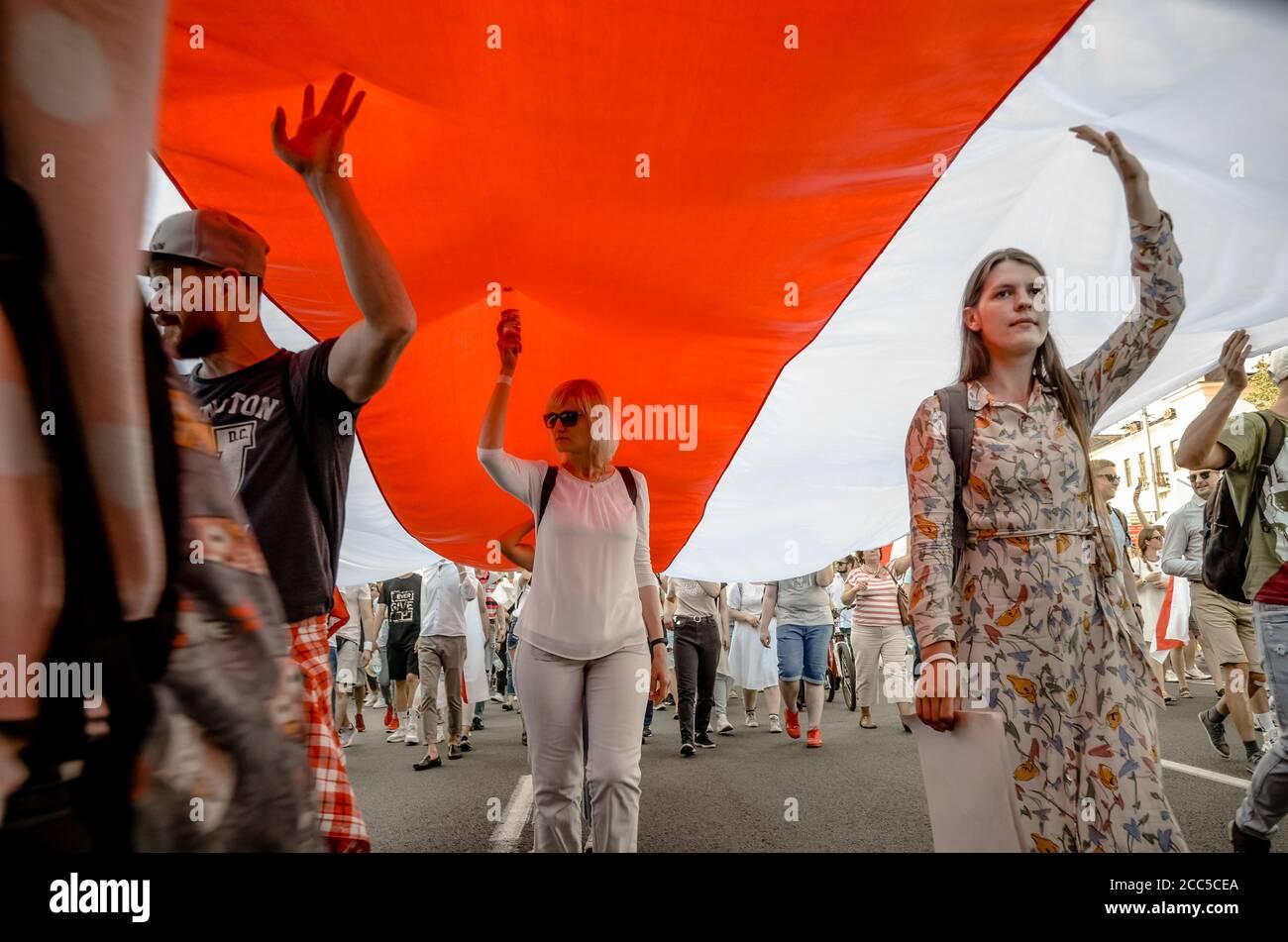 Minsk, Bielorrusia - 16 de agosto de 2020: El pueblo bielorruso lleva bandera histórica gigante de Bielorrusia. Participan en protestas pacíficas después de la presidencia de el Foto de stock