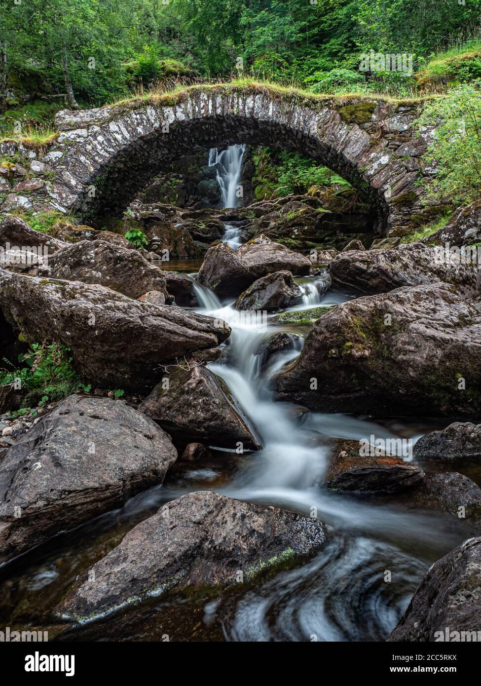 Un puente de caballo de empaquetamiento cruzando un afluente por debajo de una cascada en la orilla sur del río Lyon. Esto es conocido localmente como el Puente Romano, aunque actua Foto de stock