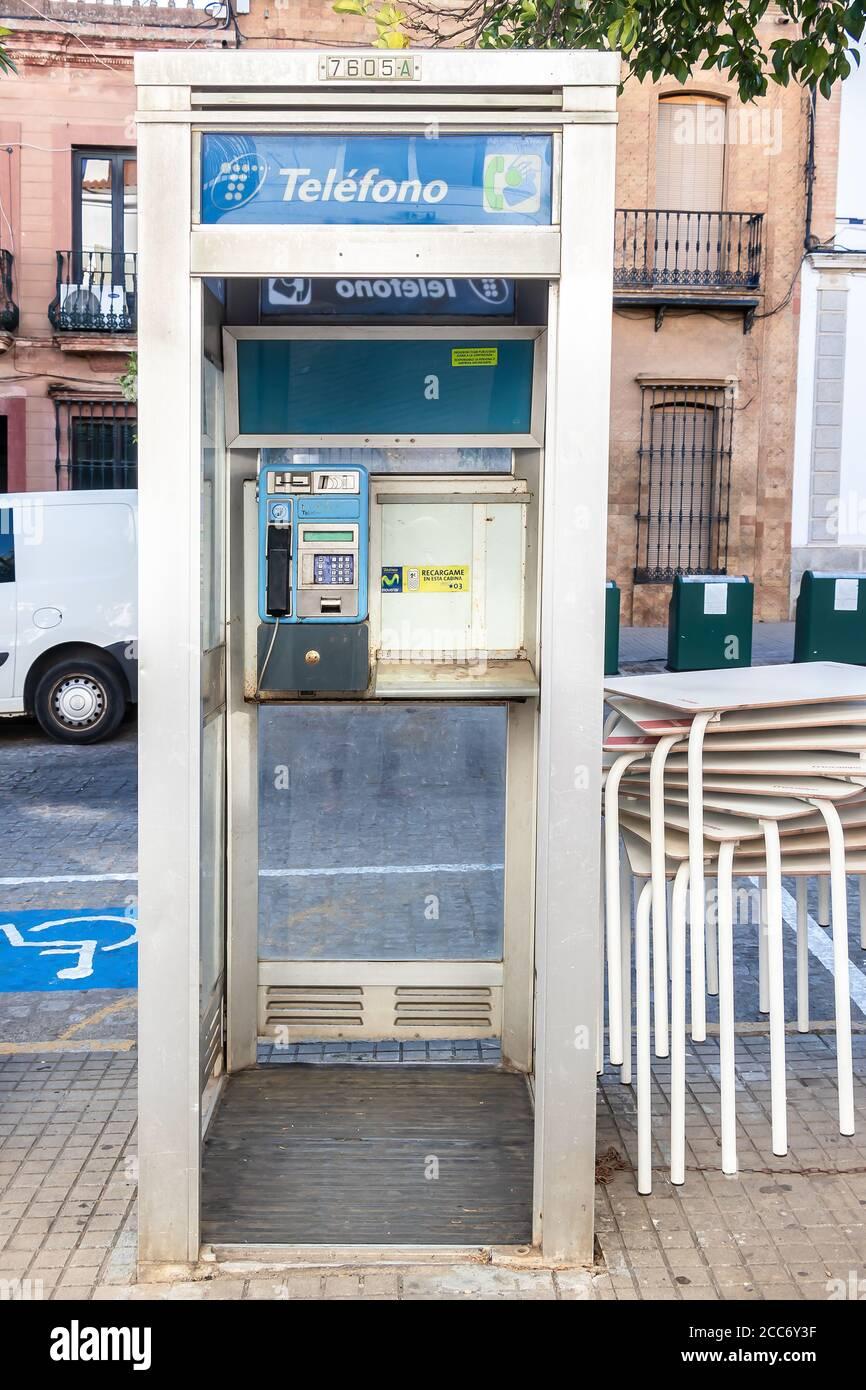 Huelva, España - 16 de agosto de 2020: Cabina telefónica de la empresa telefónica en el centro de la ciudad de Valverde del camino. Uno de los viejos e inútiles teléfonos públicos t Foto de stock