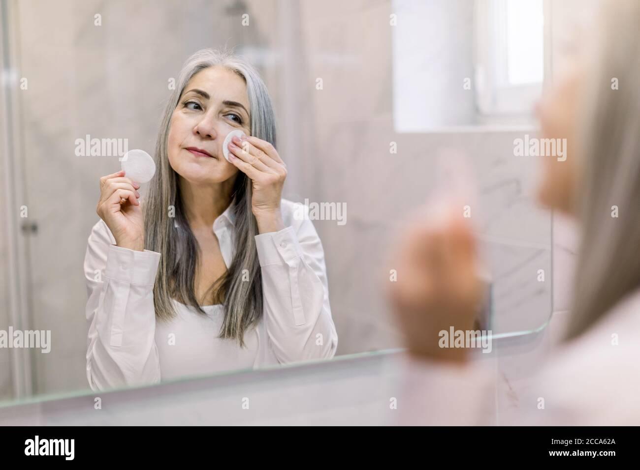 Concepto de cuidado e higiene de la piel. Encantadora señora mayor de pelo gris usando una almohadilla de algodón con agua micelar para eliminar el relleno de la cara, de pie Foto de stock