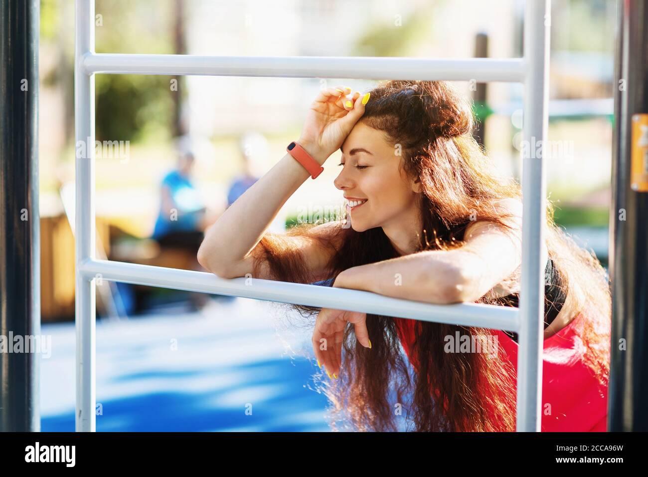 Retrato de una mujer joven de vacaciones en un campo deportivo en el parque Foto de stock