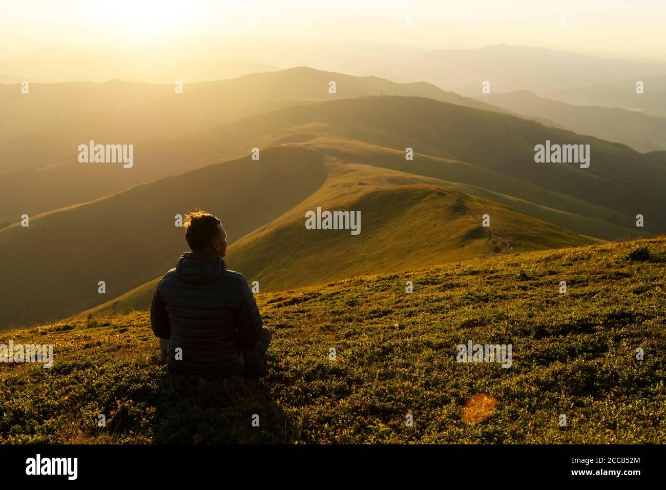 Solo turista en el borde de la colina de montaña contra el telón de fondo de un increíble paisaje de montañas al atardecer Foto de stock