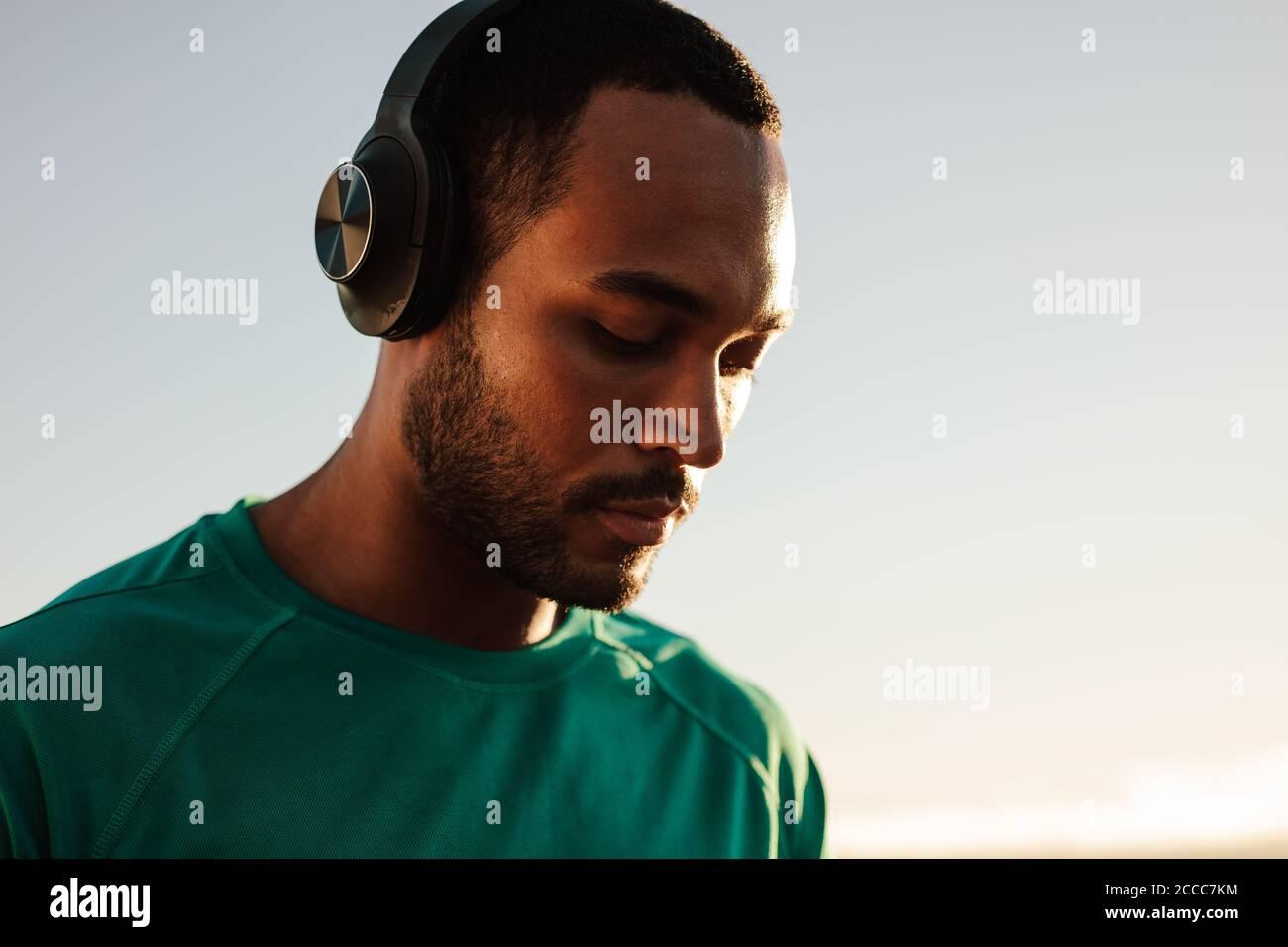 Retrato de un atleta afroamericano con auriculares inalámbricos. Primer plano de un hombre de fitness de pie al aire libre escuchando música. Foto de stock