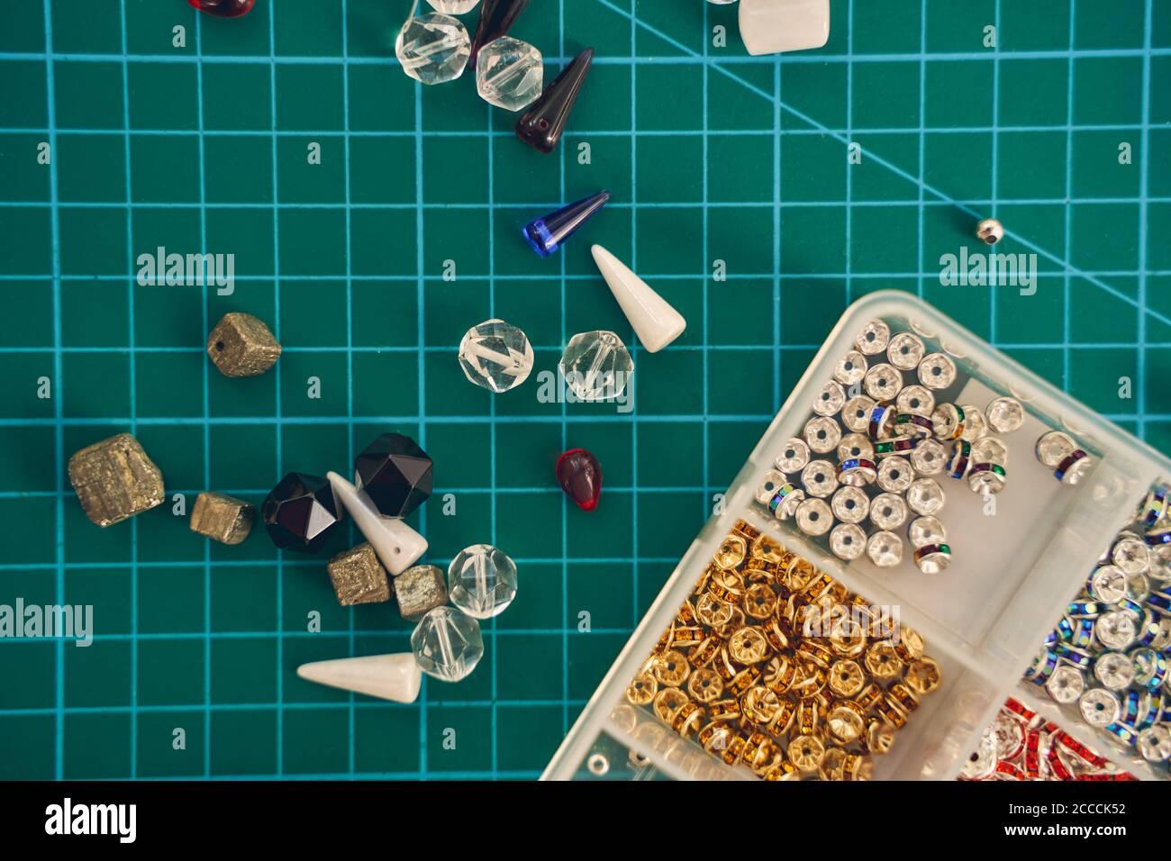Cuentas de vidrio y semillas o de fieltro para la fabricación de joyas fondo verde Foto de stock