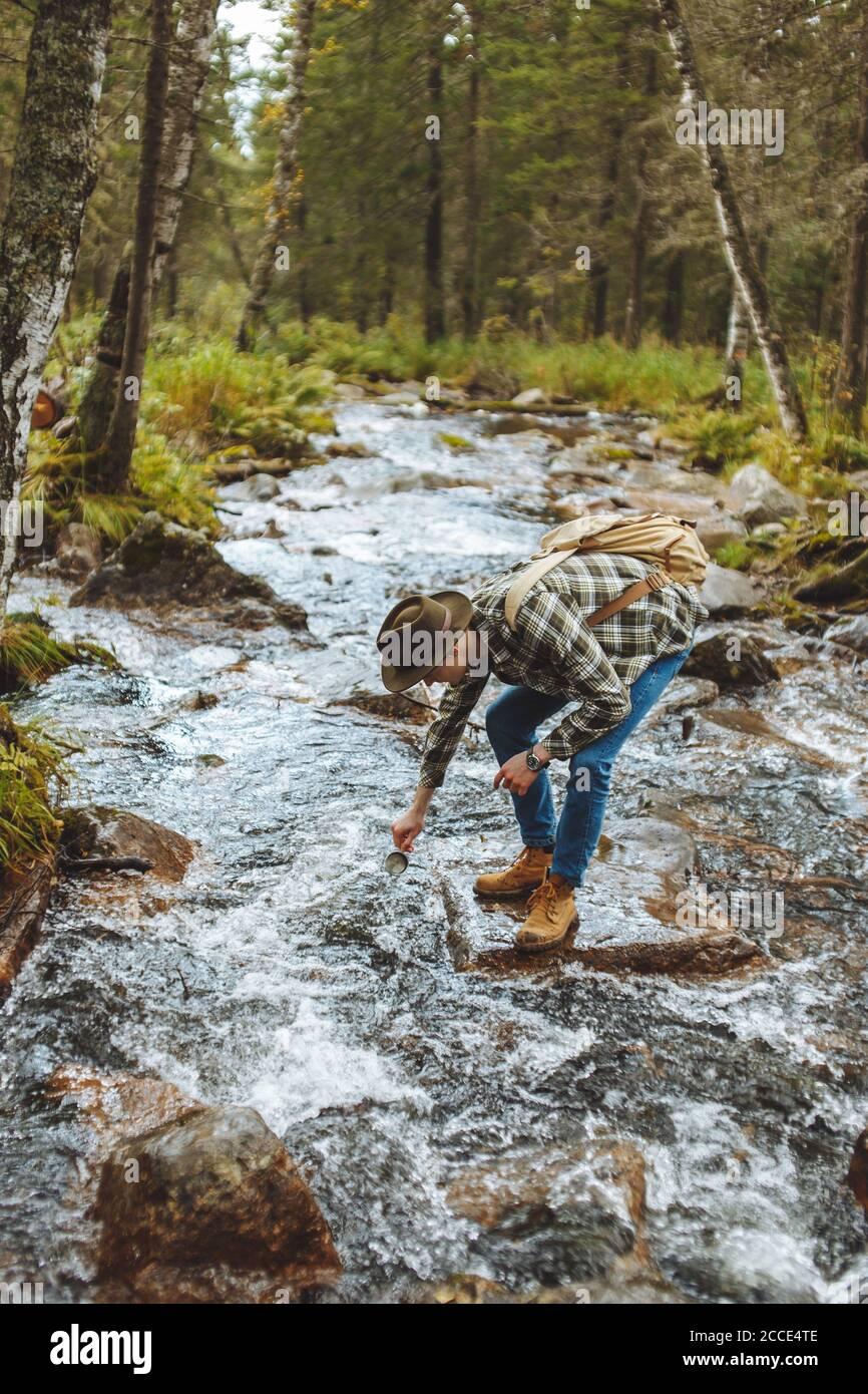 el joven hiker atrae agua fría en su taza, vista lateral completa photo.break Foto de stock