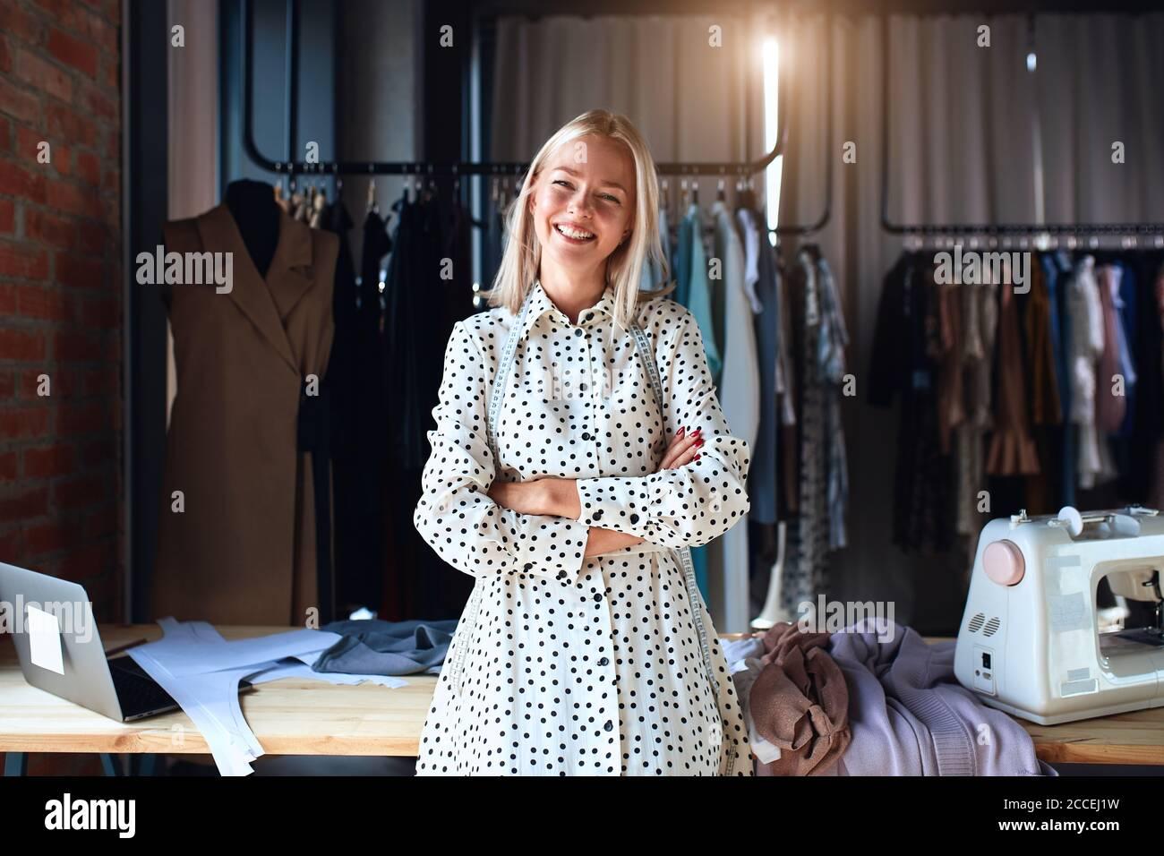 Hermoso puesto de diseñador de moda caucásico y felizmente sonrisa en el lugar de trabajo, mirar la cámara. Vestido con vestido blanco. Estudio de diseño de fondo Foto de stock